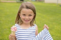 Uroczy i piękny blond młodej dziewczyny lat je wyśmienicie lody ono uśmiecha się szczęśliwy na zielonej trawy pola półdupkach Obrazy Stock