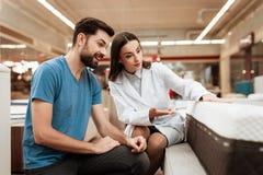 Uroczy kobieta konsultant demonstruje ortopedyczną materac ufny mężczyzna w meblarskim sklepie zdjęcia stock