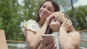 Uroczy młodej dziewczyny obsiadanie w przedpolu texting na telefonie komórkowym Beztroski przyjaciel biega w górę ona za i zamyka zbiory