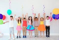 Uroczy małe dzieci przy przyjęciem urodzinowym indoors obrazy stock