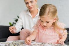 uroczy małe dziecko bawić się z łamigłówka kawałkami podczas gdy matka zdjęcie stock
