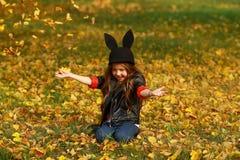 Uroczy małej dziewczynki miotania jesieni liście w piękno parku Obrazy Stock