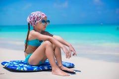 Uroczy małej dziewczynki obsiadanie na surfboard przy Obrazy Royalty Free