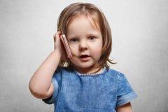 Uroczy mały żeński dzieciak, modnego uczesanie, jest ubranym drelichową modną suknię, używa nowożytnego mądrze phon dla komunikac obraz stock