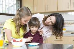Uroczy Macierzysty i jej dzieci ma śniadanie Obrazy Royalty Free