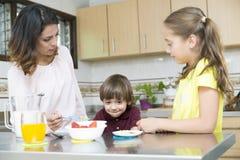 Uroczy Macierzysty i jej dzieci ma śniadanie Zdjęcia Stock