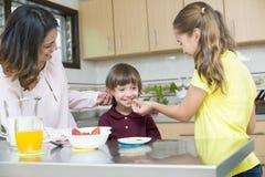 Uroczy Macierzysty i jej dzieci ma śniadanie Zdjęcia Royalty Free