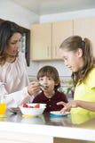 Uroczy Macierzysty i jej dzieci ma śniadanie Obraz Royalty Free
