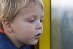 Uroczy mali blondyny żartują chłopiec siedzi blisko nadokiennego i patrzeje outside fotografia royalty free