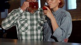Uroczy pary obejmowanie podczas gdy pijący piwo wpólnie przy restauracją zbiory