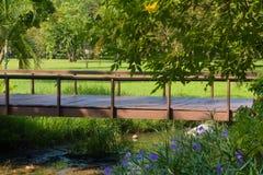 Uroczy pokojowy widok parkowy most, rozciąga się małą zatoczkę, i otaczający luksusowym ogródem obraz royalty free