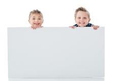 Uroczy rodzeństwa trzyma pustego białego sztandar i ono uśmiecha się przy kamerą Fotografia Stock