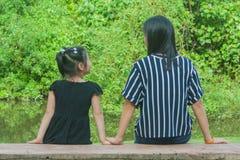 Uroczy Rodzinny pojęcie: Azjatycka kobieta, dzieci i relaksujemy na beton długiej ławce Obraz Stock