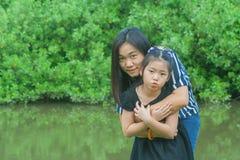 Uroczy Rodzinny pojęcie: Azjatycka kobieta i dzieci stoi na zielonej trawie, ono uśmiecha się i ściskamy wpólnie Obrazy Stock