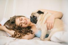 Uroczy rodzinny weekend Kobieta relaksuje w łóżku z mopsa psem Zdjęcie Stock