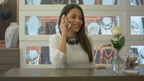 Uroczy sprzedawcy konsultant ma ślicznego ono uśmiecha się i rozmowę telefonicza w sklepie jubilerskim obraz royalty free