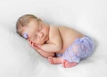 Uroczy sypialny nowonarodzony z rękami pod głową w fiołkowych majtasach zdjęcia stock