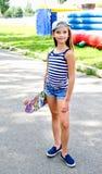 Uroczy szczęśliwy uśmiechnięty małej dziewczynki dziecko z deskorolka outdoo fotografia royalty free