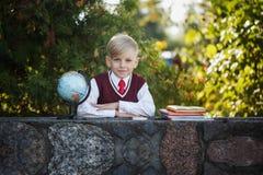 Uroczy uczeń z książkami dalej i kulą ziemską outdoors Edukacja dla dzieciaków tylna koncepcji do szkoły Obrazy Royalty Free