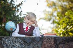 Uroczy uczeń z książkami dalej i kulą ziemską outdoors Edukacja dla dzieciaków tylna koncepcji do szkoły Zdjęcie Stock