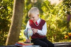 Uroczy uczeń z książkami dalej i kulą ziemską outdoors Edukacja dla dzieciaków tylna koncepcji do szkoły Zdjęcia Royalty Free