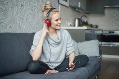 Uroczy w średnim wieku blond kobiety obsiadanie na kanapie w ona domowa i słucha muzyka obrazy royalty free