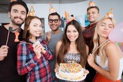 Urodzinowa dziewczyna trzyma tort z świeczkami Dziewczyny i faceci stoją wokoło ona Obraz Royalty Free