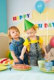 urodzinowego torta łasowania dzieciaki bawją się dwa Zdjęcia Royalty Free