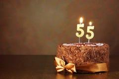 Urodzinowy czekoladowy tort z płonącymi świeczkami jak liczbę pięćdziesiąt pięć Fotografia Stock