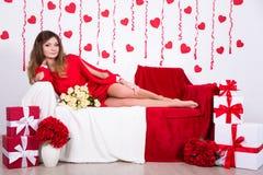 Urodzinowy pojęcie - wspaniała kobieta w długim czerwieni sukni obsiadaniu w d obrazy royalty free