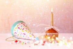 Urodzinowy pojęcie z babeczką i świeczką Błyskotliwość zaświeca narzutę zdjęcie stock