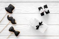 Urodzinowy prezent dla mężczyzna Zawijający pudełko, ciastka w kształcie czarny krawat, wąsy, kapelusz Białego drewnianego tła od Fotografia Royalty Free