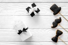 Urodzinowy prezent dla mężczyzna Zawijający pudełko, ciastka w kształcie czarny krawat, wąsy, kapelusz Białego drewnianego tła od Obraz Stock