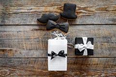 Urodzinowy prezent dla mężczyzna Zawijający pudełko, ciastka w kształcie czarny krawat, wąsy, kapelusz Drewnianego tła odgórny wi Zdjęcia Stock