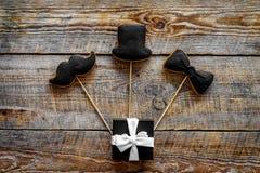 Urodzinowy prezent dla mężczyzna Zawijający pudełko, ciastka w kształcie czarny krawat, wąsy, kapelusz Drewnianego tła odgórny wi Zdjęcie Stock