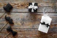 Urodzinowy prezent dla mężczyzna Zawijający pudełko, ciastka w kształcie czarny krawat, wąsy, kapelusz Drewniany tło odgórnego wi Obraz Stock
