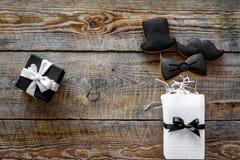 Urodzinowy prezent dla mężczyzna Zawijający pudełko, ciastka w kształcie czarny krawat, wąsy, kapelusz Drewniany tło odgórnego wi Fotografia Stock