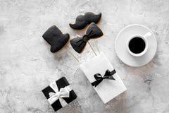 Urodzinowy prezent dla mężczyzna Zawijający pudełko, ciastka w kształcie czarny krawat, wąsy, kapelusz Popielatego tła odgórny wi Zdjęcie Stock