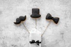 Urodzinowy prezent dla mężczyzna Zawijający pudełko, ciastka w kształcie czarny krawat, wąsy, kapelusz Popielatego tła odgórny wi Obrazy Stock