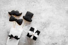 Urodzinowy prezent dla mężczyzna Zawijający pudełko, ciastka w kształcie czarny krawat, wąsy, kapelusz Popielaty tło odgórnego wi Obrazy Stock