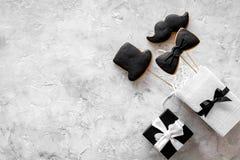 Urodzinowy prezent dla mężczyzna Zawijający pudełko, ciastka w kształcie czarny krawat, wąsy, kapelusz Popielaty tło odgórnego wi Obraz Stock