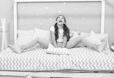 Urodzinowy ranek Dziewczyna dziecko siedzi na łóżkowy szczęśliwym patrzeje up Dzieciak obudzony i pełno energia Przyjemny czas re obraz stock