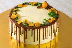 Urodzinowy tort z kremową czekoladą kapie na złocistym tle Zdjęcia Stock