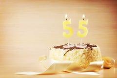 Urodzinowy tort z płonącą świeczką jako numerowy pięćdziesiąt pięć Fotografia Royalty Free