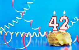 Urodziny czterdzieści dwa roku Babeczka z białą płonącą świeczką w postaci liczby 42 obraz royalty free