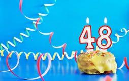 Urodziny czterdzieści osiem rok Babeczka z białą płonącą świeczką w postaci liczby 48 obraz stock