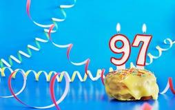 Urodziny dziewięćdziesiąt siedem rok Babeczka z białą płonącą świeczką w postaci liczby 97 obraz royalty free