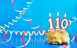 Urodziny sto i dziesięć rok Babeczka z białą płonącą świeczką w postaci liczby 110 obraz stock