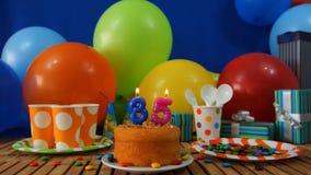 Urodziny 35 tort na nieociosanym drewnianym stole z tłem kolorowi balony, prezenty, plastikowe filiżanki, klingerytu talerz obrazy royalty free