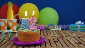 Urodziny 52 tort z świeczkami na nieociosanym drewnianym stole z tłem kolorowi balony, prezenty, plastikowe filiżanki i cukierki, zdjęcie stock